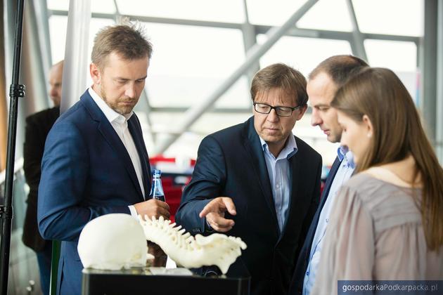 Tomasz Szymański (w okularach) prezentuje wydruki z Vshaper